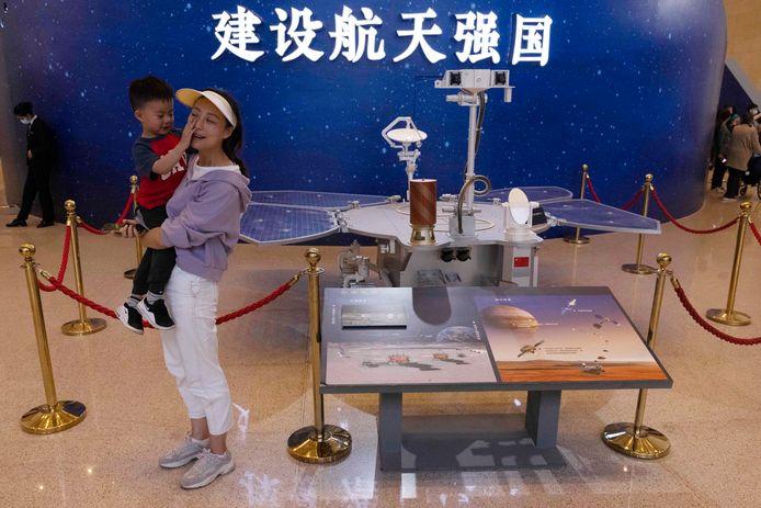 Bezoekers poseren bij een model van de Chinese Mars-rover Zhurong in het Nationaal Museum van Peking.