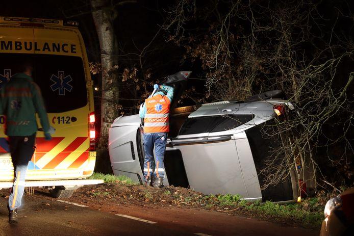 De BMW is op de zijkant in de sloot terechtgekomen. Ambulancepersoneel kijkt of er nog iemand in de auto zit.