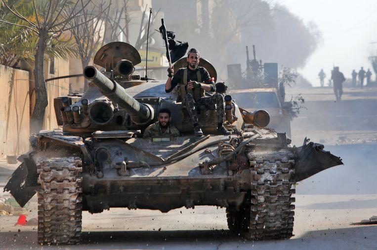Syrische rebellenstrijders vrijdag, bijgestaan door Turkse troepen rijden in Saraqib, een plaats in het oosten van de provincie Idlib.  Beeld AFP