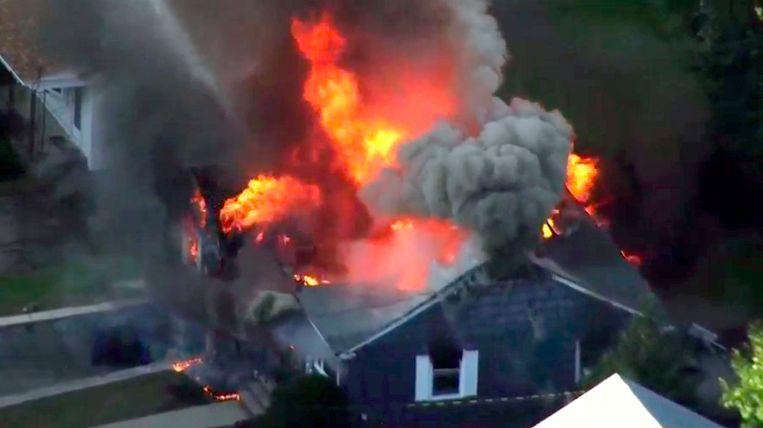 Brandweerlieden bestrijden het vuur in een huis in Lawrence. Beeld AP