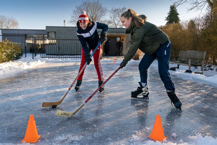Anemone Arntz (links) en haar vriendin Nina Willigers spelen een potje ijshockey.