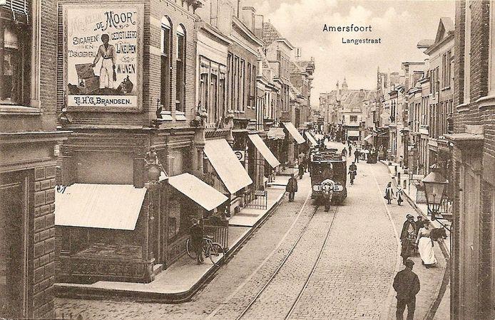 De paardentram nadert rond 1907 de Varkensmarkt, de oorspronkelijke foto. Rechts lopen drie dames en daarachter twee kinderen. Links staat een man bij zijn fiets, die voor de etalage staat. Naast de paardentram komt een man aanwandelen en achter de tram rijdt een fietser.