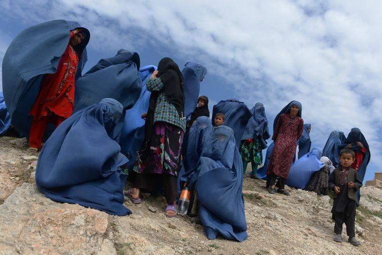 Een foto van Afghaanse dorpelingen in 2014, nadat hun dorp is getroffen door een landverschuiving.  Beeld AFP