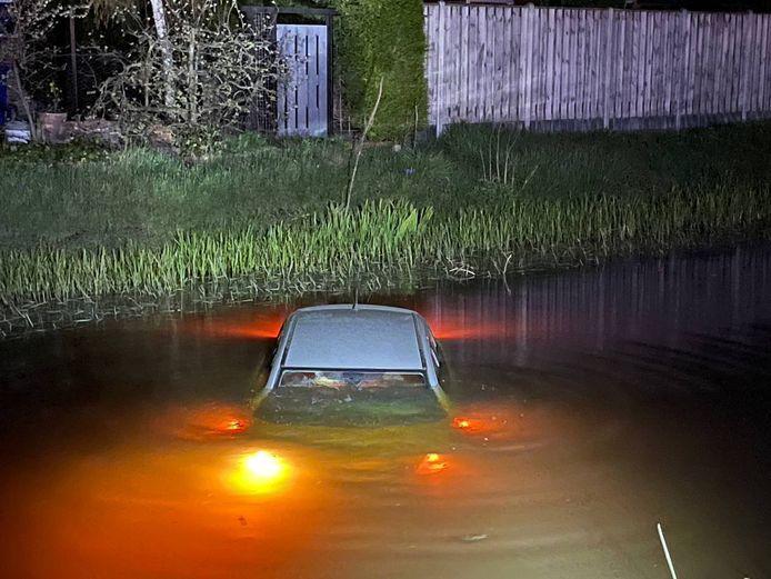 De auto ligt bijna helemaal onderwater en de lichten zijn gaan branden, waarschijnlijk door het contact met het water.