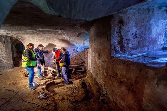 Bouwhistoricus Frank Haans in overleg met Ester van der Linden en Caroline den Hartog (beiden archeoloog) en projectleider Martien Knoops. In de kelder van het Wijchens kasteel waar een oude fundering is ontdekt, uit de 14e eeuw. Foto: Eveline van Elk