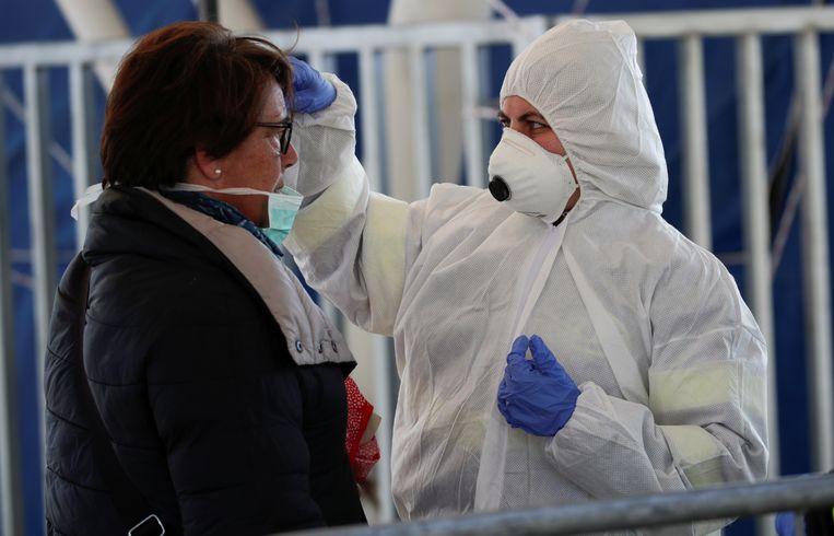 Een man in beschermende kledij meet de temperatuur van een vrouw in Napels. Zuid-Italië bereidt zich voor op de onvermijdelijke uitbraak van het coronavirus.  Beeld REUTERS