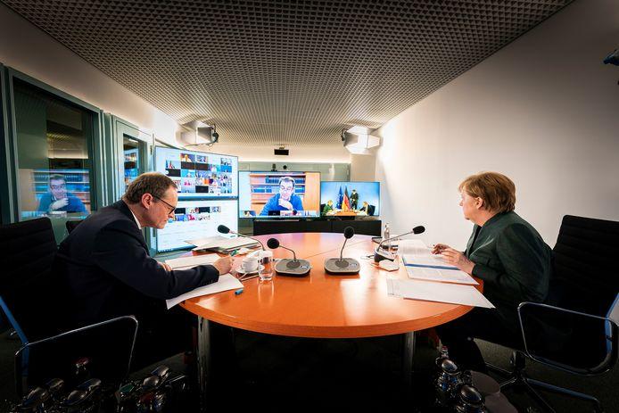 Bondskanselier Angela Merkel (r) met de Berlijnse burgemeester Michael Müller die de videovergadering met de minister-presidenten van de deelstaten voorzit.