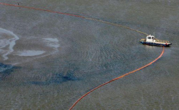 Een boot plaatst olieschermen om te voorkomen dat de olievlek zich verder verspreid. ANP Beeld