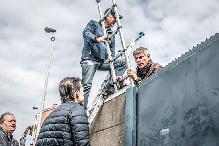 Filip De Winter klimt over de poort van het asielcentrum.