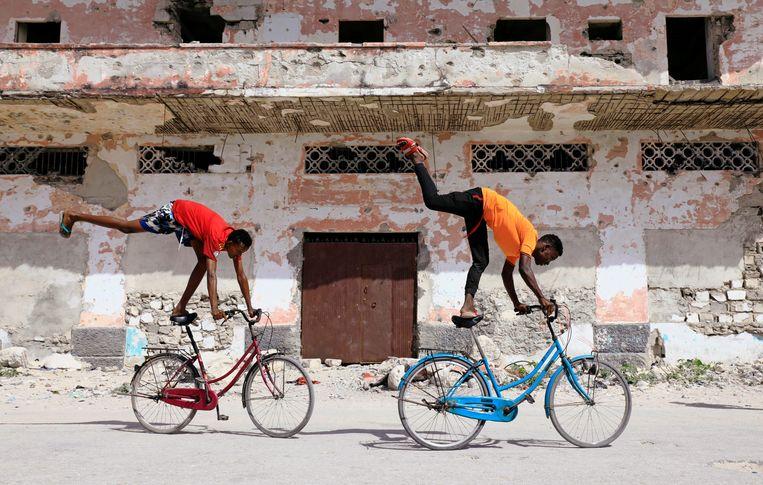 Twee Somalische jongens doen truckjes op hun fietsen in de hoofdstad Mogadishu. Beeld REUTERS