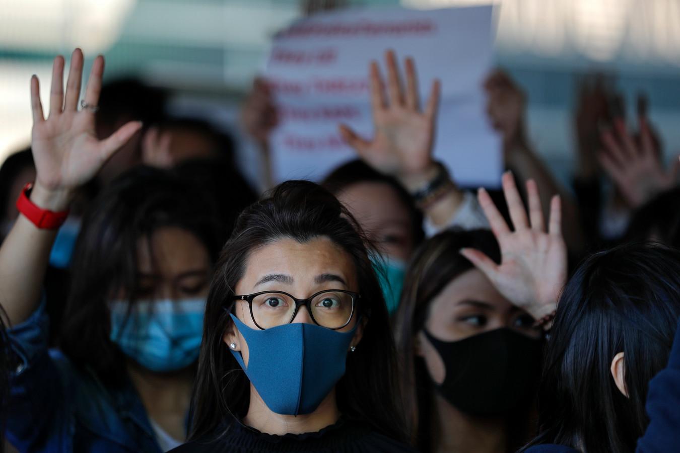Pro-democratie-demonstranten in Hong Kong houden hun uitgestoken hand op en symboliseren zo de vijf eisen van de beweging.