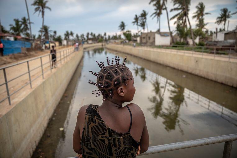 Een jonge vrouw aan de reling van een nieuw gebouwd afwateringskanaal. Beeld Sven Torfinn