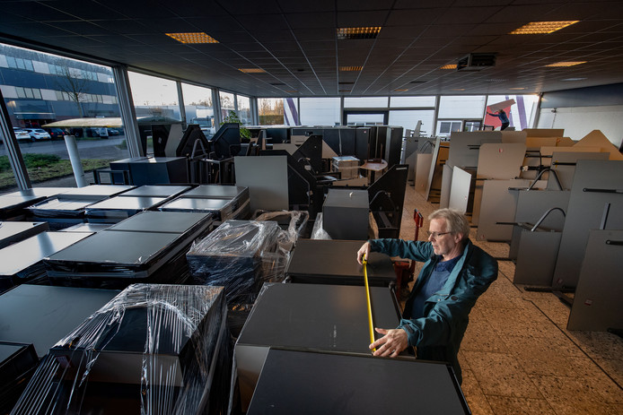 Dominee Wim Terlouw meet een kast op in de volle showroom, met allemaal overbodig meubilair van de gemeente Dronten.