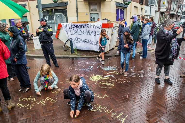 Kinderen schrijven zaterdag met krijt hun klachten op de stoep over de verloedering van een deel van de Haagse Weimarstraat. Beeld Arie Kievit