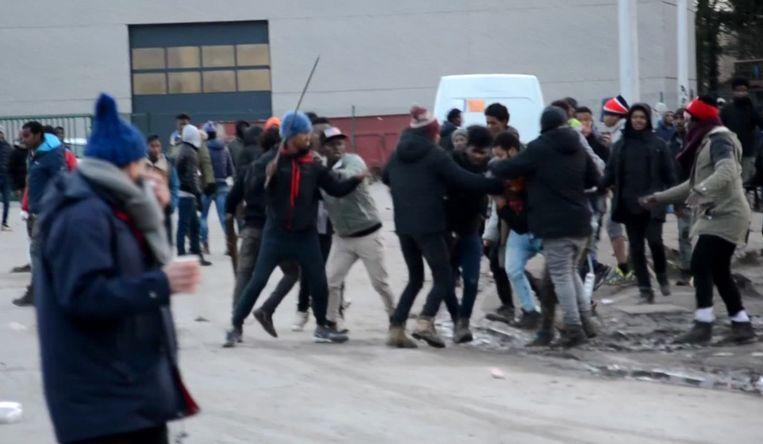 Vooraleer de schoten werden afgevuurd bevochten Eritrese en Afghaanse transmigranten elkaar met stokken nabij de haven van Calais. Beeld AP