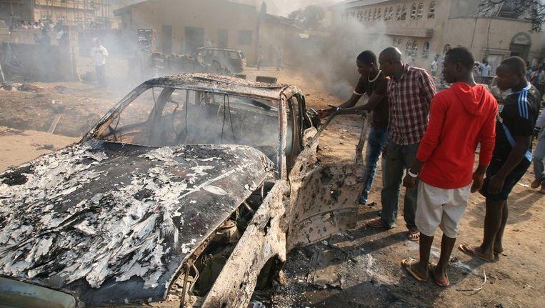 Omstanders bekijken de resten van een auto op de plek waar een bom is ontploft. Beeld afp
