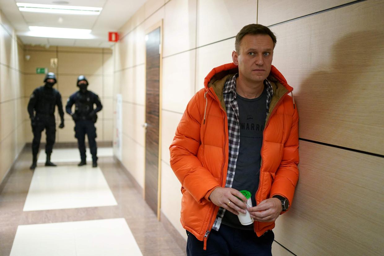 Aleksej Navalny op een beeld van vorig jaar, met agenten op de achtergrond. Navalny slaagde erin een FSB'er allerlei details te laten vertellen over de aanslag op hemzelf aan de telefoon. Beeld AFP