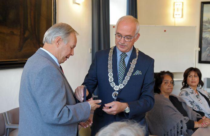 Burgemeester Mulder reikt het oorlogskruis uit aan de de zoon van Frits Portier.