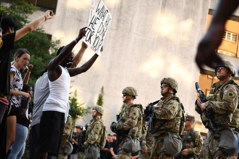 Demonstranten van Black Lives Matter worden door een politiecordon tegengehouden. Beeld AFP