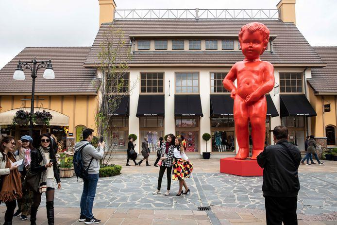 Chinezen poseren dolblij aan het beeld.