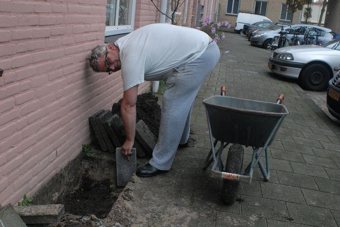 Loek Dingarten plant een lei-kersenboom tegen de gevel van z'n woning.