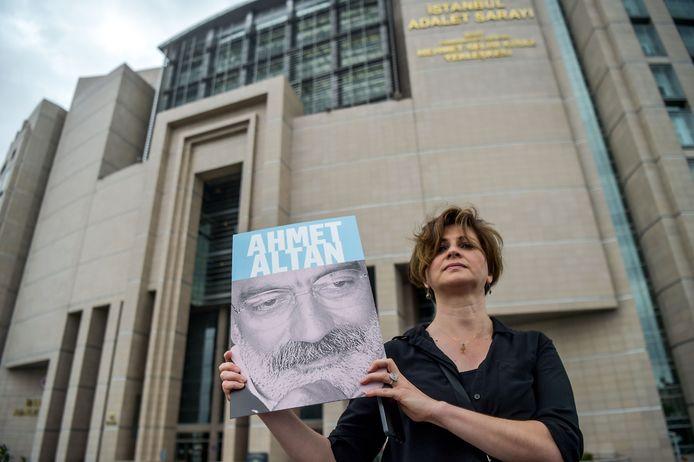 Een journalist staat met het portret van Ahmet Altan voor de rechtbank in Istanboel waar zijn proces plaatsvindt.