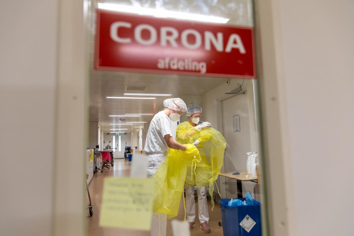 Verpleegkundigen maken zich klaar om de afdeling te verlaten; gele schorten en handschoenen worden uitgetrokken, de rest gaat pas af als ze door de deuren zijn.