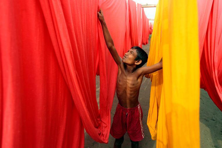 Een kind aan het werk in een stoffenfabriek in Bangladesh. Beeld AP