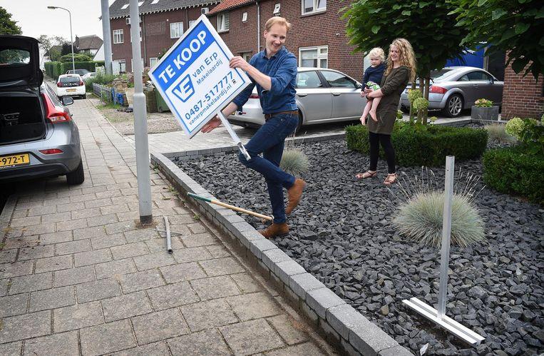 Een makelaar plaatst een te koop-bord in de voortuin Beeld Marcel van den Bergh / de Volkskrant