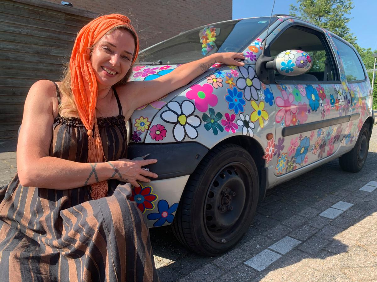 Cindy van Kuyen poseert met haar auto 'Maria', die elke keer als ze door de keuring komt een 'bos bloemen' krijgt opgeplakt. Het is daardoor een vrolijke wagen geworden.