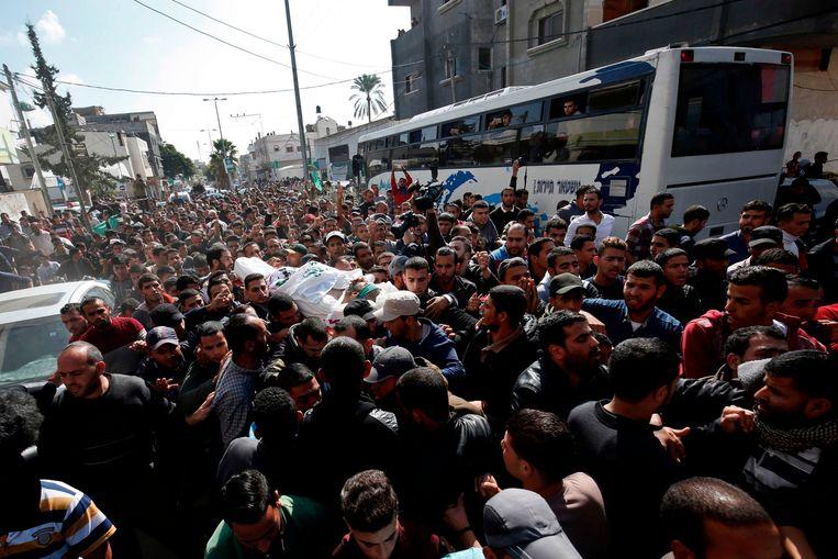 Grote menigte helpt bij het dragen van de overleden Hamas-strijder.   Beeld AFP