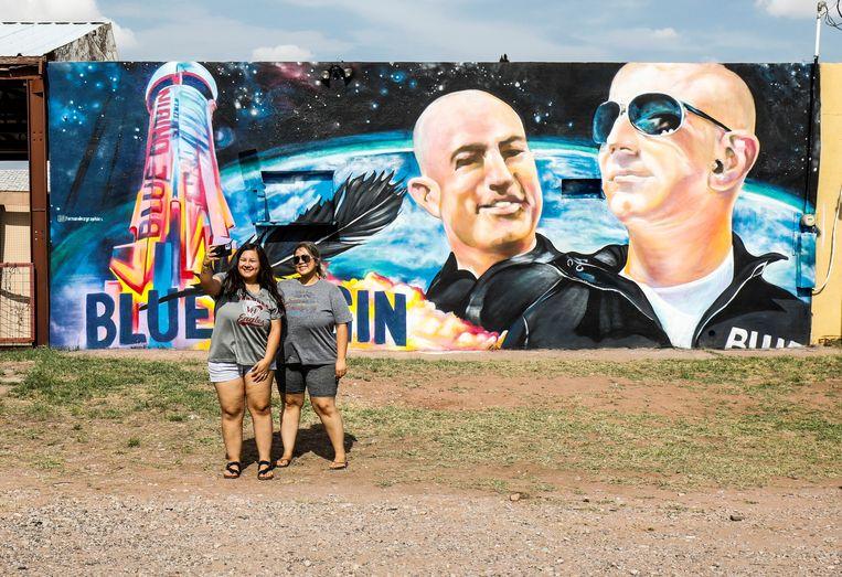 Twee Texaanse vrouwen nemen een selfie bij een mural van Jeff Bezos en zijn broer Mark in Van Horn, Texas. Beeld REUTERS