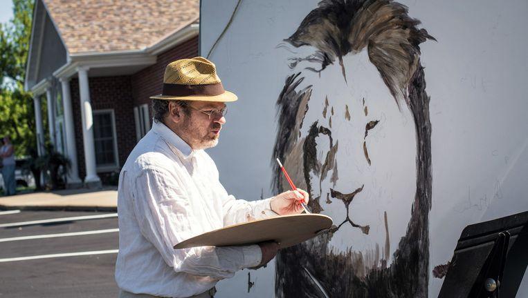 Schilder Mark Balma maakt een portret van Cecil, de Zimbabwaanse leeuw die begin juli werd doodgeschoten door een Amerikaanse tandarts. Beeld ap