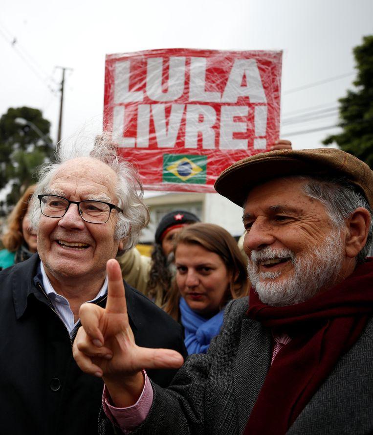 De Argentijnse Nobelprijswinnaar voor de Vrede, Adolfo Perez Esquivel (links) arriveert met voormalig Braziliaans minister van Buitenlandse zaken Celso Amorim (rechts)  om oud-president Luiz Inacio Lula da Silva te bezoeken in het hoofdkwartier van de federale politie.   Beeld REUTERS
