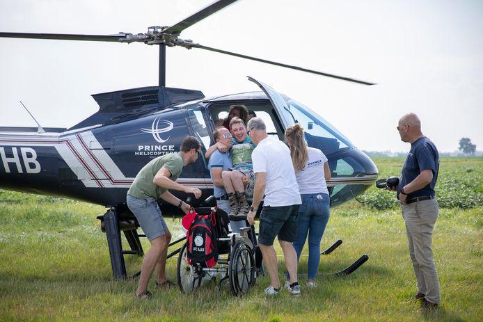 Kevin Keepers is klaar voor zijn helikoptervlucht. Met blauw shirt helpt Mark Deckers van Stichting Allstarz hem de heli in.
