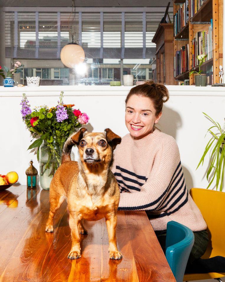 Laura van der Haar en haar hond Takkie, gefotografeerd in haar huis in Amsterdam-West. Beeld Hilde Harshagen