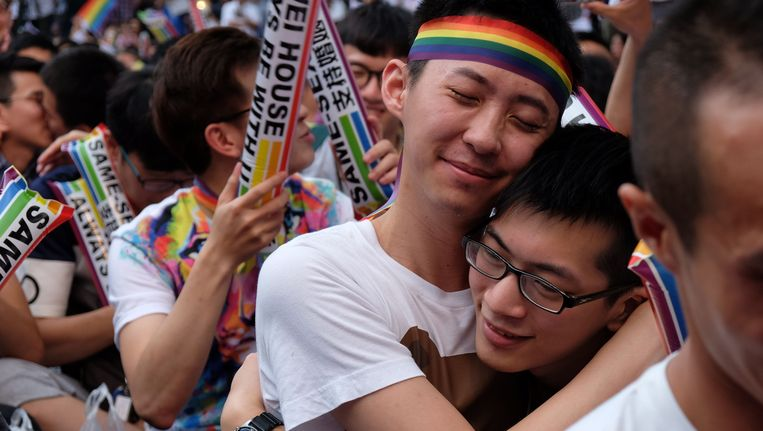 Homokoppels verzamelen voor het parlement in Taipei en omarmen elkaar wanneer ze vernemen dat het homohuwelijk er eindelijk gelegaliseerd wordt. Beeld AFP