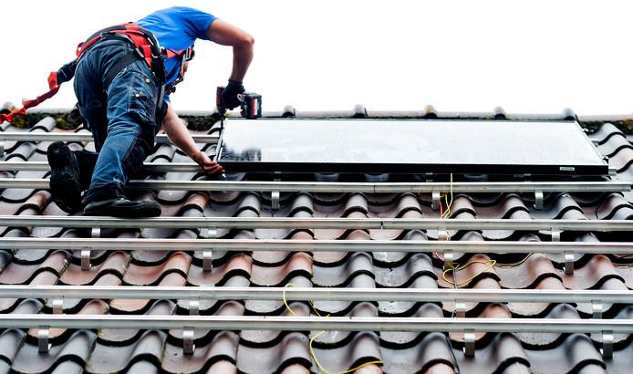 Een monteur plaats zonnepanelen op het dak van een woonhuis. ANP KOEN VAN WEEL