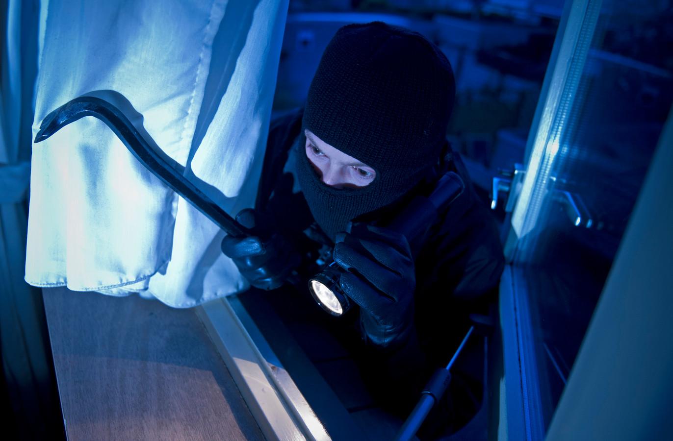 In scene gezette foto van een inbreker die met behulp van een koevoet een woning binnendringt. Ook één van de twee inbrekers die in Wilp een woning binnendrong, had een koevoet.