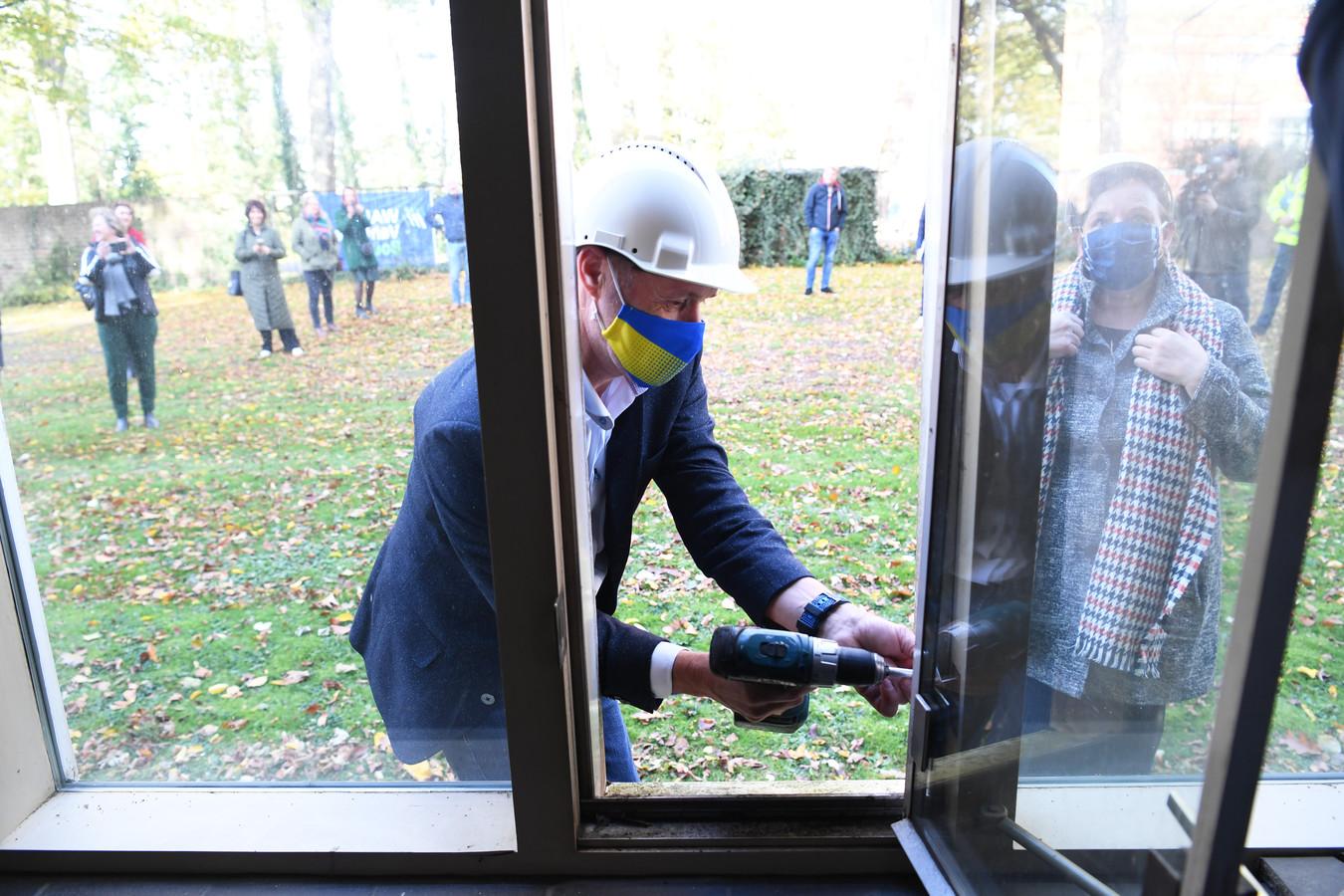 Wethouder John van den Hoven en museumbestuurslid Margo Strik verwijderen een raam. Het is het officiële startsein voor de bouw van het nieuwe schoenenmuseum.