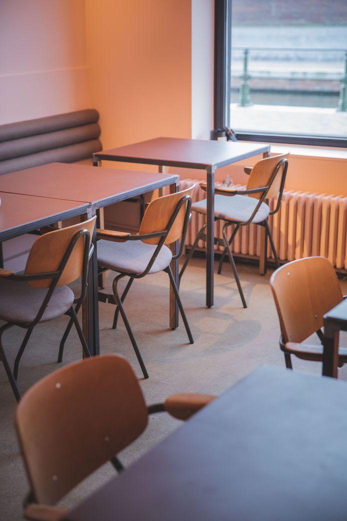 Doorheen de zaal werden er stalen tafeltjes neergezet met houten, bestofte stoelen rond.