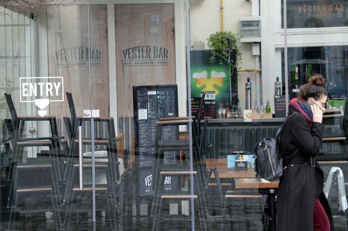 Een vrouw wandelt voorbij een gesloten restaurant in Brussel.