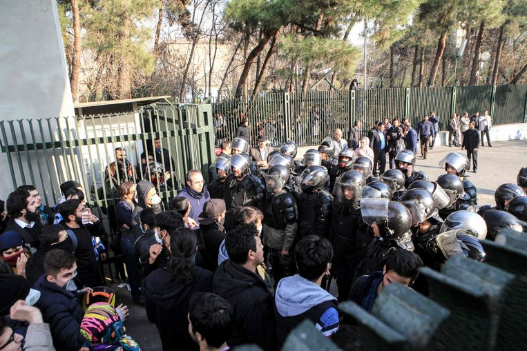 ► Confrontatie tussen betogers en ordetroepen aan de universiteit van Teheran. Het protest is veel feller dan in 2009. Beeld AFP