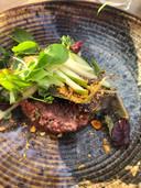 De steak tartaar met mosterdschuim, cornichon, eigeel en desemkrokant.