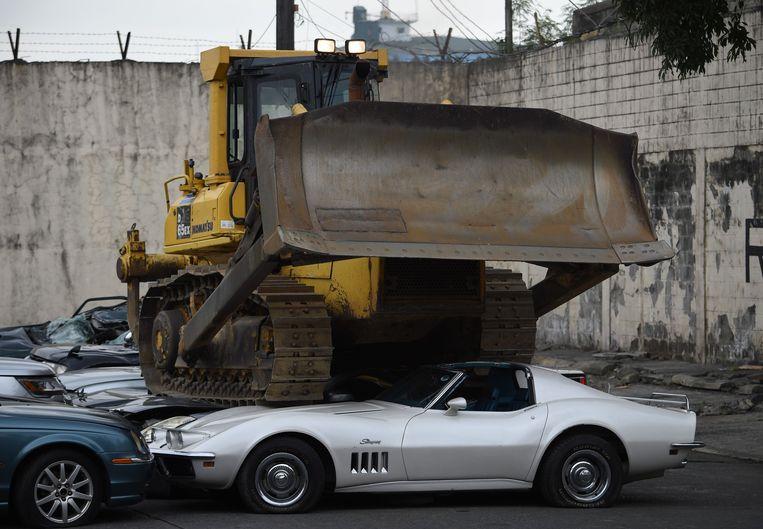 De Filipijnse president Rodrigo Duterte liet een bulldozer los op 20 luxe-wagens. Beeld AFP