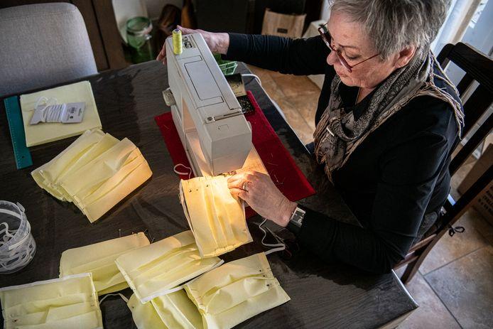 Jeanne van Ooijen bezig met het maken van mondkapjes