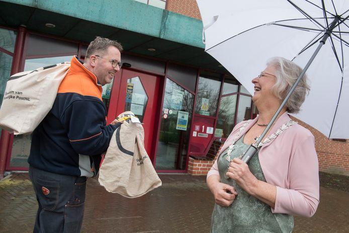 Josan Meijers lacht met een postbode buiten het gemeentehuis in Maurik.