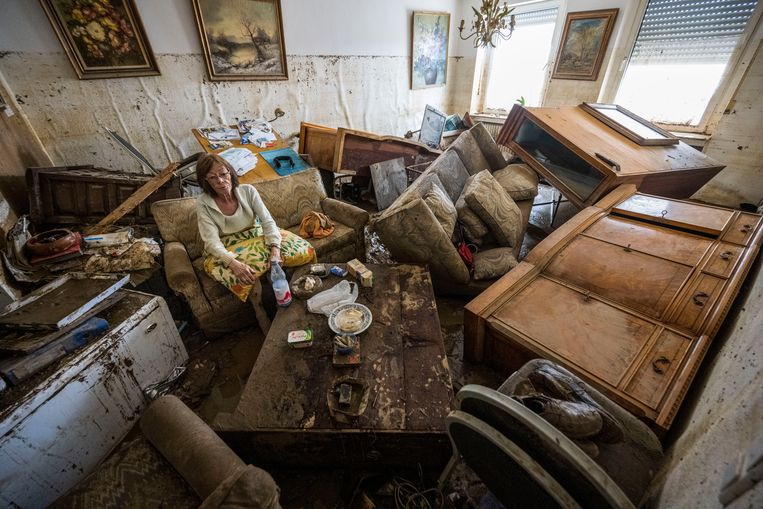 Een vrouw zit in haar verwoeste woonkamer in het Duitse Bad Neuenahr.  Beeld Getty Images