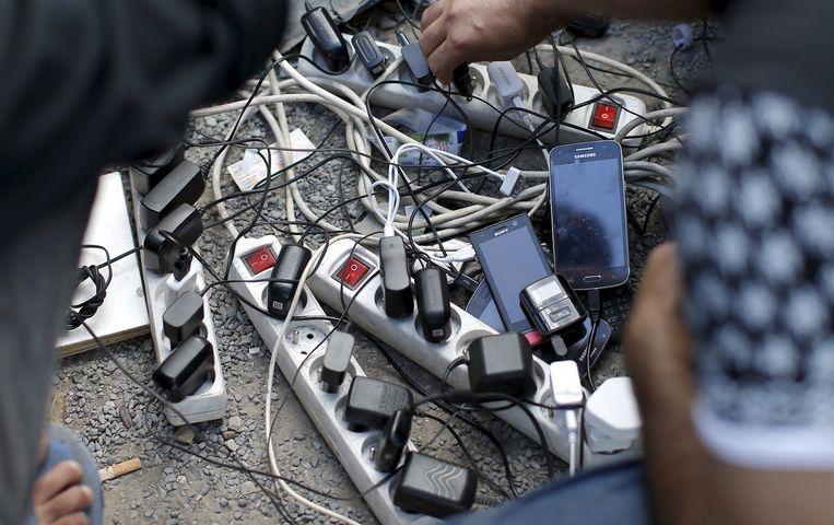 Vluchtelingen uit Afghanistan laden hun mobiele telefoons op in de jungle van Calais. Beeld REUTERS