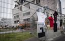 Aan de ingestorte school hangen bloemen, tekeningen en T-shirts om de vijf omgekomen arbeiders te herdenken.